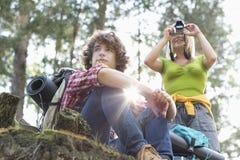 Młody żeński wycieczkowicz fotografuje przez cyfrowej kamery podczas gdy mężczyzna patrzeje daleko od w lesie Obraz Stock