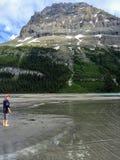 Młody żeński wycieczkowicza chodzić bosy na mokrych piasków bankach Góra lodowa jezioro z ariergardy górą w tle zdjęcie stock