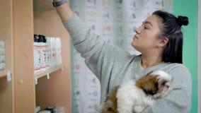 Młody żeński zwierzę domowe właściciel wybiera szampon dla jej psa w sklepie, trzyma ślicznego shih tzu szczeniaka na rękach zbiory