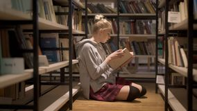 Młody żeńskiego ucznia czytelniczy obsiadanie między półkami na książki zdjęcie wideo