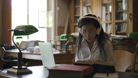 Młody żeńskiego ucznia prawnik jest czytelniczym książką, pisać na maszynie na laptopu obsiadaniu w bibliotece zbiory
