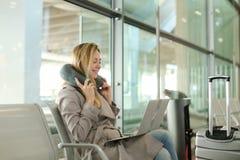 Młody żeńskiej osoby obsiadanie w poczekalni z laptopem blisko valise, używać szyi poduszkę Zdjęcie Stock