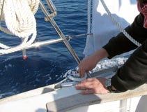 Młody żeglarz na winch w żaglówka kokpicie obrazy royalty free