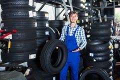 Młody życzliwy mechanika mężczyzna pracuje z samochodowymi oponami w warsztacie obraz royalty free