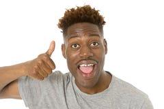 Młody życzliwy, szczęśliwy afro amerykański mężczyzna ono uśmiecha się excited i pozować chłodno i rozochocony odosobnionego Fotografia Stock