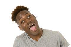 Młody życzliwy, szczęśliwy afro amerykański mężczyzna ono uśmiecha się excited i pozować chłodno i rozochocony odosobnionego Obraz Stock