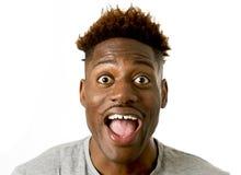 Młody życzliwy, szczęśliwy afro amerykański mężczyzna ono uśmiecha się excited i pozować chłodno i rozochocony odosobnionego Obrazy Stock