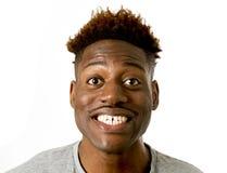 Młody życzliwy, szczęśliwy afro amerykański mężczyzna ono uśmiecha się excited i pozować chłodno i rozochocony odosobnionego Zdjęcia Stock