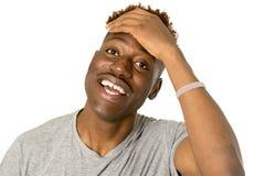 Młody życzliwy, szczęśliwy afro amerykański mężczyzna ono uśmiecha się excited i pozować chłodno i rozochocony odosobnionego Zdjęcie Stock