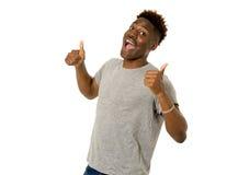 Młody życzliwy, szczęśliwy afro amerykański mężczyzna ono uśmiecha się excited i pozować chłodno i rozochocony odosobnionego Obrazy Royalty Free