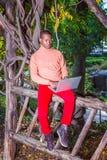 Młody Africain Amerykański mężczyzna pracuje na laptopie na zewnątrz a zdjęcie stock