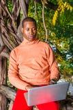 Młody Africain Amerykański mężczyzna pracuje na laptopie na zewnątrz a zdjęcia stock