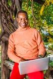 Młody Africain Amerykański mężczyzna pracuje na laptopie na zewnątrz a obraz royalty free