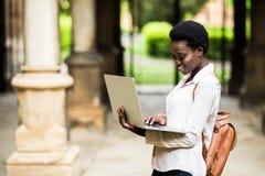 Młody afro amerykański dziewczyna uczeń pisać na maszynie outdoors w kampusie z laptopem obraz stock