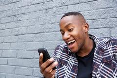 Młody afro amerykański facet czyta śmieszną wiadomość tekstową Obrazy Royalty Free