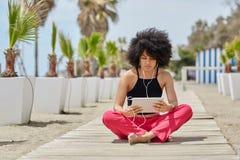 Młody afro amerykański kobiety obsiadanie krzyżujący iść na piechotę słuchającą muzykę f Zdjęcia Stock