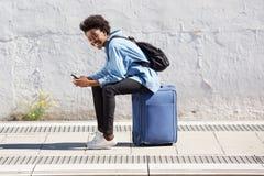 Młody afro amerykański kobiety obsiadanie na walizce przy kolejową platformą z telefonem komórkowym Zdjęcie Royalty Free