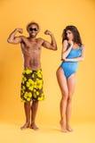 Młody afro amerykański mężczyzna pokazuje bicepsy jego dziewczyna Zdjęcia Royalty Free