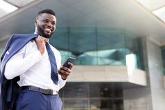 Młody afrykański biznesmen trzyma jego telefon podczas gdy stojący pełno radość zdjęcia stock