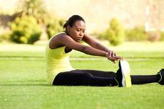 Młody afrykański kobiety obsiadanie na trawy rozciąganiu dosięgać palec u nogi Fotografia Stock