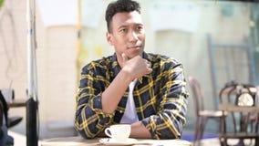 Młody afrykański mężczyzna myśleć nowego pomysł, plenerowa kawiarnia zbiory