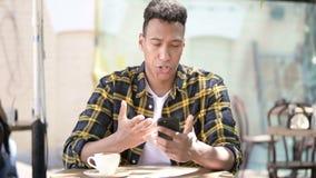 Młody afrykański mężczyzna niepokojący stratą na smartphone, plenerowa kawiarnia zbiory wideo