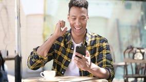 Młody afrykański mężczyzna odświętności sukces na smartphone, plenerowa kawiarnia zdjęcie wideo