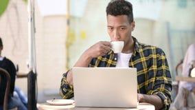 Młody afrykański mężczyzna pije kawę i działanie na laptopie, plenerowa kawiarnia zbiory wideo