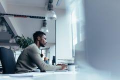Młody afrykański mężczyzna pracuje w biurze Fotografia Royalty Free