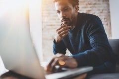 Młody Afrykański mężczyzna używa laptop przy jego nowożytnym coworking miejscem podczas gdy siedzący Pojęcie ludzie biznesu pełne obraz stock