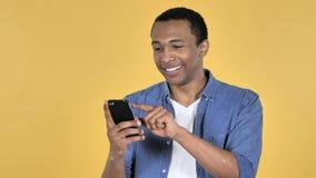 Młody Afrykański mężczyzna Wyszukuje Smartphone, Żółty tło zdjęcie wideo