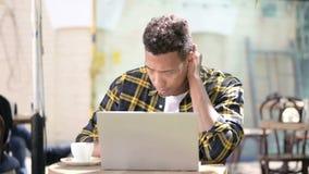 Młody afrykański mężczyzna z szyja bólem używać laptop, plenerowa kawiarnia zbiory wideo