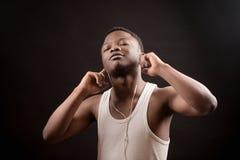 Młody Afrykański męski słuchanie muzyka z zamkniętymi oczami zdjęcie stock