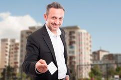 Młody agent nieruchomości pokazuje pustą kartę Zdjęcie Stock