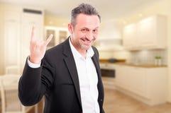 Młody agent nieruchomości robi rockowemu gestowi Zdjęcie Royalty Free