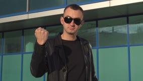 Młody agresywny mężczyzna w skórzanej kurtce i okularach przeciwsłonecznych pokazuje pięść plenerowych pozycję i zdjęcie wideo
