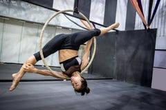 Młody akrobatyczny kobiety obwieszenie na powietrznym obręczu Zdjęcia Stock