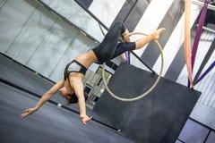 Młody akrobatyczny kobiety obwieszenie na powietrznym obręczu Zdjęcie Royalty Free