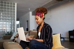 Młody amerykański afrykański żeński blogger pracuje daleko na cyfrowym netbook z interneta tekstem Afrykański kobiety copywriter zdjęcia stock