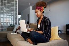 Młody amerykański afrykański żeński blogger pracuje daleko na cyfrowym netbook z interneta tekstem Afrykański kobiety copywriter obraz royalty free