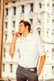 Młody Amerykański biznesmen opowiada na telefonie komórkowym outside Obrazy Royalty Free