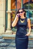 Młody Amerykański bizneswoman opowiada na telefonie komórkowym outside Zdjęcia Stock