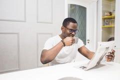 Młody amerykanin afrykańskiego pochodzenia biznesmen czyta gazetę przy śniadaniem zdjęcie royalty free