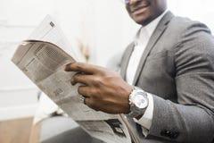 Młody amerykanin afrykańskiego pochodzenia biznesmen czyta gazetę w szarym kostiumu podczas gdy siedzący na kanapie obraz royalty free