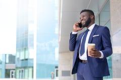 Młody amerykanin afrykańskiego pochodzenia biznesmen mówi klient na telefonie z filiżanką coffe podczas przerwa czasu kosmos kopi zdjęcia stock