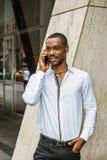 Młody amerykanin afrykańskiego pochodzenia biznesmen opowiada na telefonie komórkowym outside w Nowy Jork z brodą zdjęcia stock