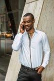 Młody amerykanin afrykańskiego pochodzenia biznesmen opowiada na telefonie komórkowym outside w Nowy Jork z brodą obrazy royalty free