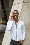 Młody amerykanin afrykańskiego pochodzenia biznesmen opowiada na telefonie komórkowym outside w Nowy Jork z brodą zdjęcie stock