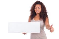 Młody amerykanin afrykańskiego pochodzenia kobiety mienia pustego miejsca znak odizolowywający na wh Obraz Royalty Free