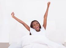 Młody amerykanin afrykańskiego pochodzenia kobiety rozciąganie w łóżku w domu Obrazy Stock